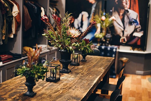 A table at Brooklyn  Circus with proteas, thistle, Queens Anne's lace, and greenery in black urns.