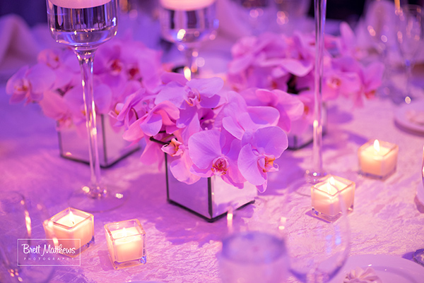 Orchid centerpieces in mirror vases.