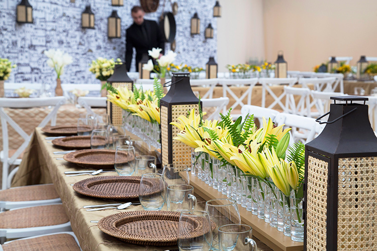 Yellow lilies and our Square Iron Lanterns with caning line a table. Note the lanterns hung on the wall.