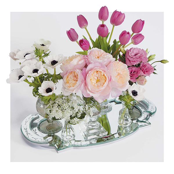 Centerpiece with gathered bunches of flowers in bud vases.