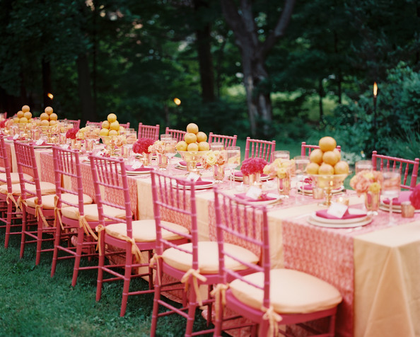A beautifully set, long, outdoor dining table.