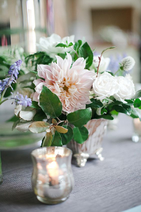Centerpiece in silver urn with greenery, dahlias, and roses