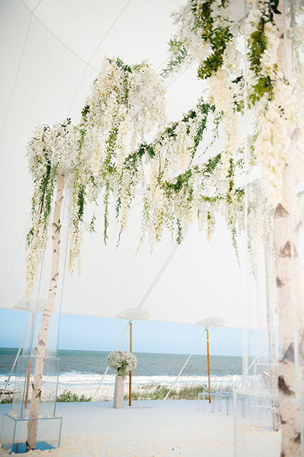 A pretty beach wedding ceremony decorated with birch poles, white flowers, and ghost chairs