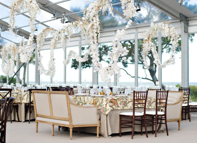 White Phalaenopsis orchids cascade over wedding reception tables