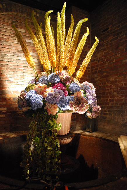 An urn holds a large arrangement with faux hydrangeas